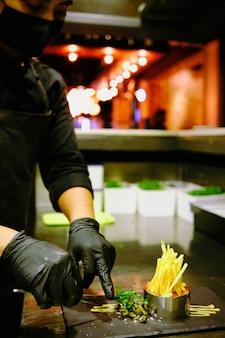 Chef-kok die gastronomische maaltijdplaat afwerkt en garneert.