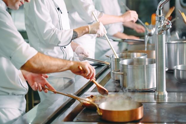 Chef-kok die groenten in wokpan koken.