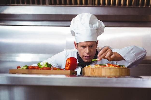 Chef-kok die groenten snijdt om op een pizza te zetten