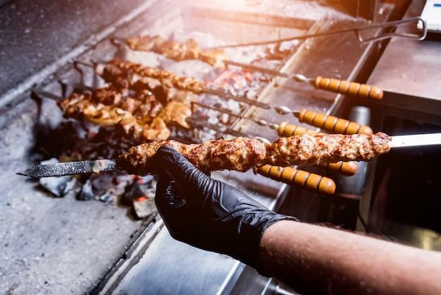 Chef-kok die heerlijke rundvlees en varkensvleesbarbecue bij de grill koken. georgisch restaurant.