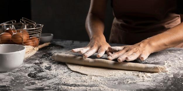 Chef-kok die het deeg met handen rolt