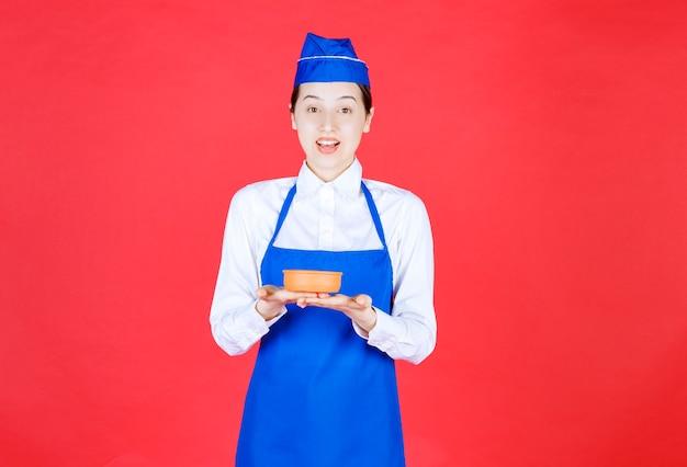 Chef-kok die in blauwe schort een aardewerkkom houdt.