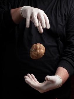 Chef-kok die in witte handschoenen vleesballen maakt