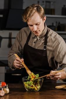 Chef-kok die ingrediënten voor de salade mengt