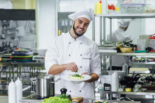 Chef-kok die italiaanse deegwarencarbonara met kaasparmezaanse kaas en met dille kookt