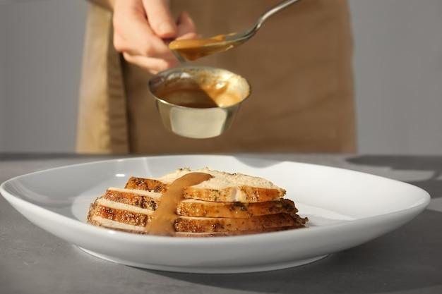 Chef-kok die kalkoenjus op gesneden vlees op plaat giet
