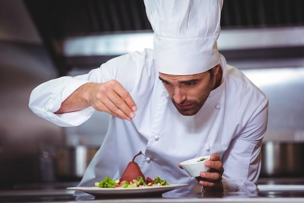 Chef-kok die kruiden op schotel bestrooien