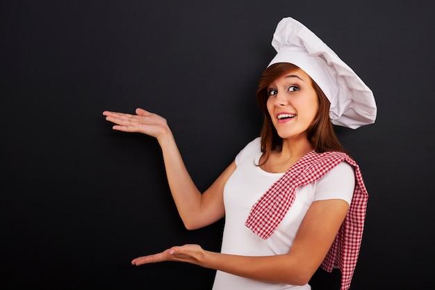 Chef-kok die leeg menu op bord toont