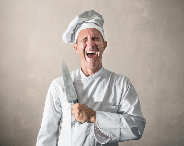 Chef-kok die met een in hand mes lacht