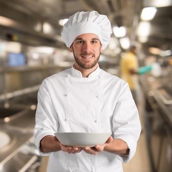 Chef-kok die met gelukkige uitdrukking zijn bord houdt