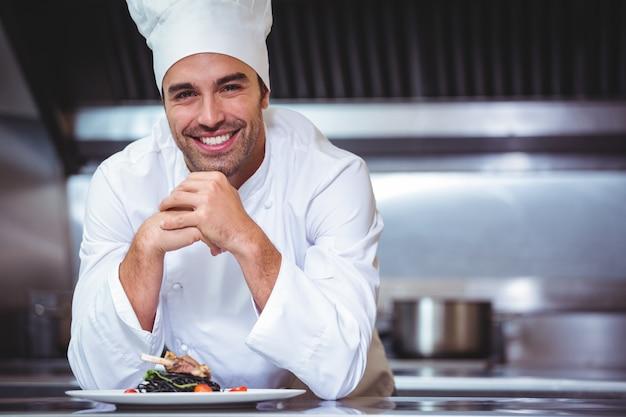 Chef-kok die op de teller met een schotel leunt