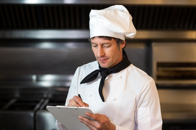 Chef-kok die op klembord in keuken schrijft