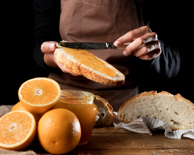 Chef-kok die oranje marmelade op brood uitspreiden
