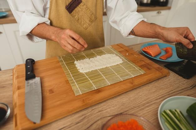 Chef-kok die perfecte sushi maakt met bamboemat close-up groothoek mannelijke handen koken op keukensushi