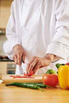 Chef-kok die rode paprika snijdt