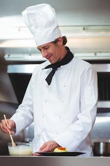 Chef-kok die saus op een schotel zet