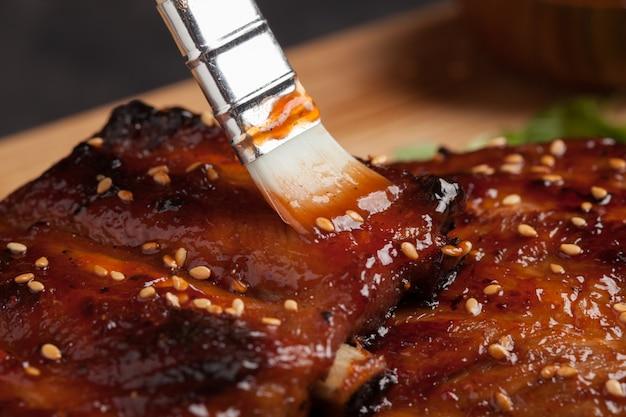 Chef-kok die sausbbq op ribben uitspreidt.
