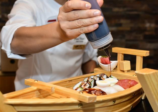 Chef-kok die sushibroodjes op plaat schikt