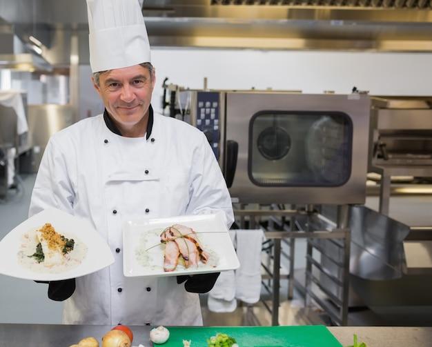 Chef-kok die twee platen in de keuken houdt