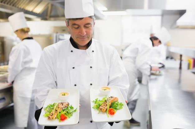 Chef-kok die twee zalmschotels in zijn handen bewondert