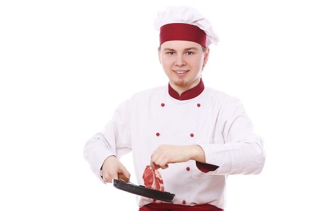 Chef-kok die vers vlees op een pan zet