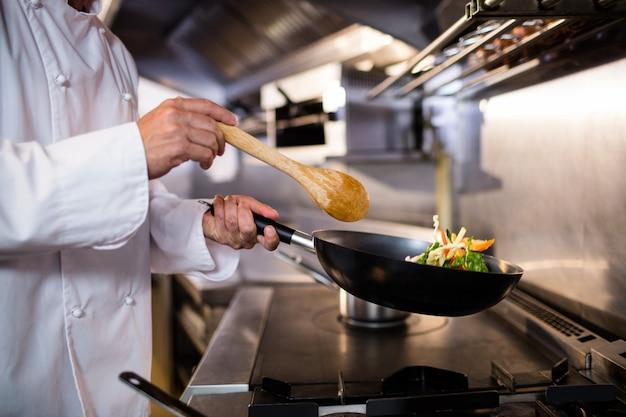 Chef-kok die voedsel in de keuken voorbereidt