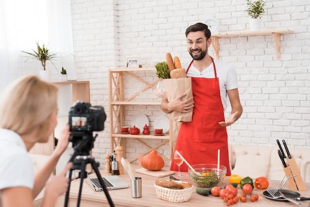 Chef-kok die voedselingrediënten voor culinaire podcastcamera presenteert.