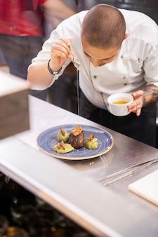 Chef-kok die zijn fijne keuken toont. professionele voedseldecoratie