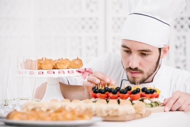 Chef-kok die zorgvuldig snacks op een lijst voorbereidt