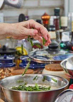 Chef-kok doopt asperges in het servies om gebakken goederen met asperges en erwten te maken. stap voor stap recept.