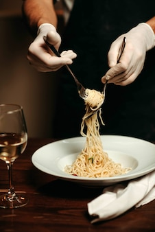 Chef-kok draait spaghetti met vork en lepel