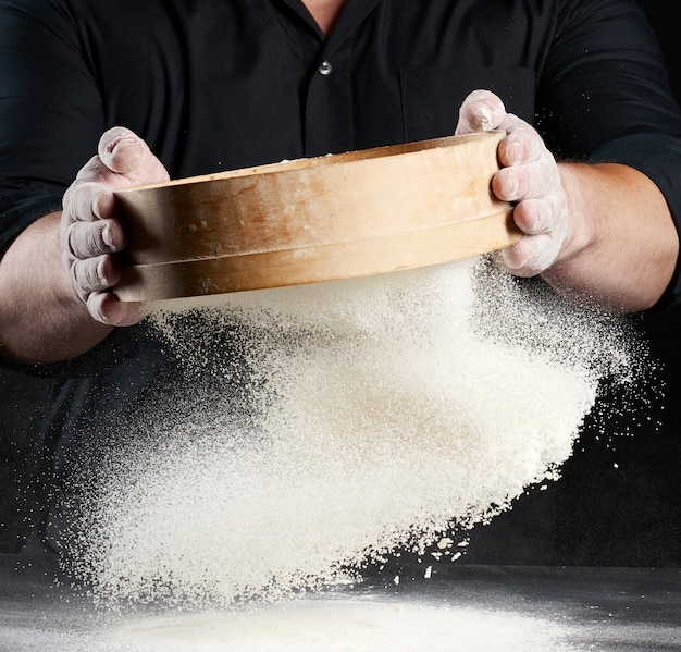 Chef-kok een man in een zwart uniform houdt een ronde houten zeef in zijn handen en zeeft wit tarwemeel op een zwarte ruimte, de deeltjes vliegen in verschillende richtingen, stoffige ruimte