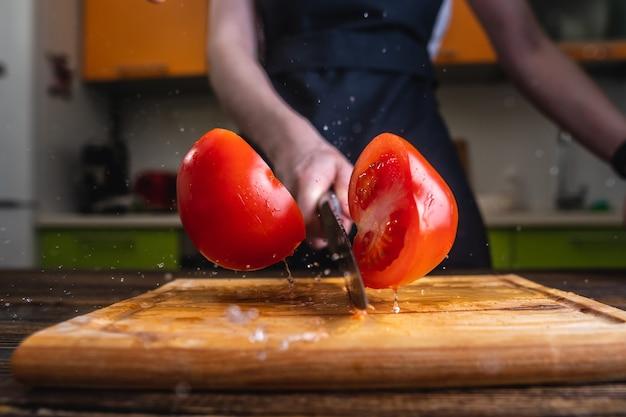 Chef-kok een rode tomaat doormidden snijden met een groot mes in beweging