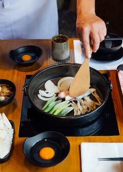 Chef-kok gebakken ui, lente-ui en champignons in hete pot van sukiyaki.