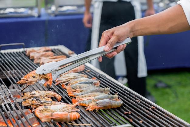 Chef-kok gegrilde rivier garnalen of thaise garnalen op barbecue kachel.