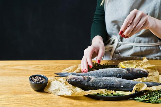 Chef-kok gezouten zeebaars op een houten tafel.