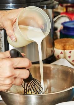 Chef-kok giet melk van maatglas in kom en roert het met garde.