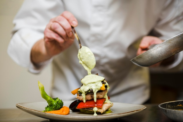 Chef-kok gieten saus over maaltijd