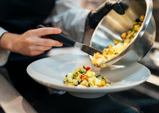 Chef-kok gieten voedsel op plaat