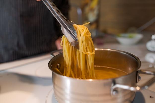 Chef-kok haalt met sleuflepel hete stomende eiernoedels uit de pan