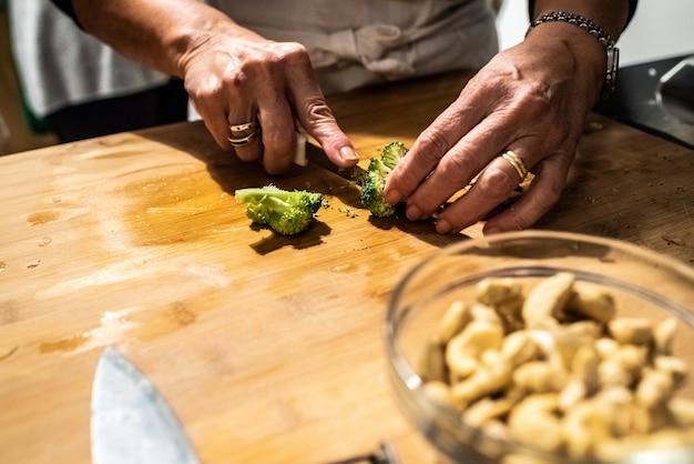 Chef-kok hakken en snijden van groenten voor een stoofpot.