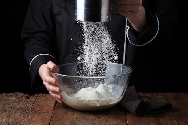 Chef-kok handen gieten meel poeder.