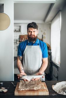 Chef-kok handen houdt rauwe vis over snijplank