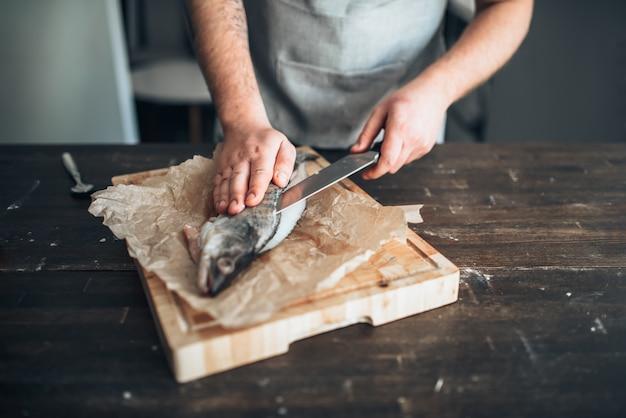 Chef-kok handen met mes gesneden vis op snijplank