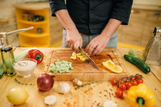 Chef-kok handen met mes snijdt gele peper op houten bord close-up.