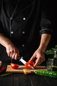 Chef-kok handen met mes, verse rode tomaten snijden voor salade
