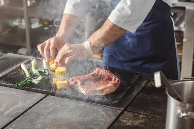Chef-kok het koken lapje vlees van het barbecue het sappige rundvlees bij restaurantkeuken