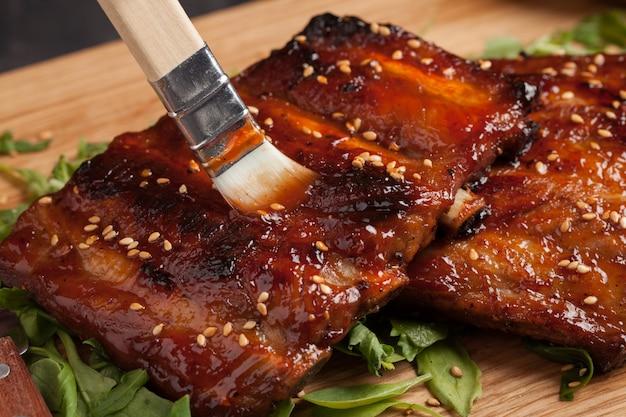 Chef-kok het spreiden sausbbq op ribben.