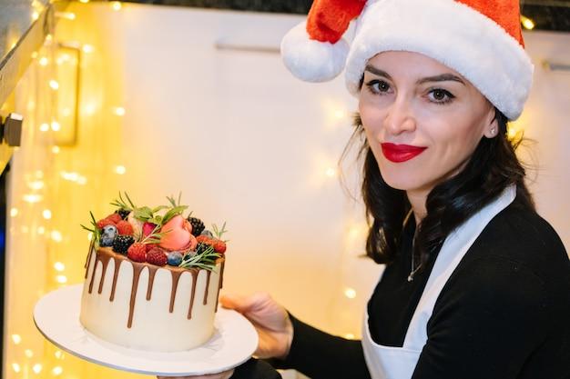 Chef-kok houdt zelfgemaakte kerstcake met fruit vast. gelukkig nieuwjaar en vrolijk kerstfeest