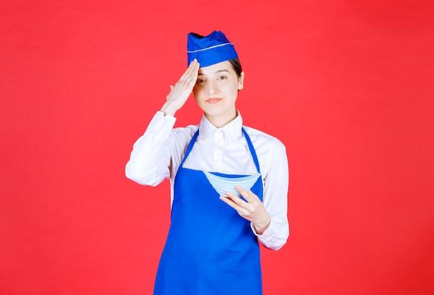 Chef-kok in blauw schort met een keramische kom met eten en ziet er moe uit.